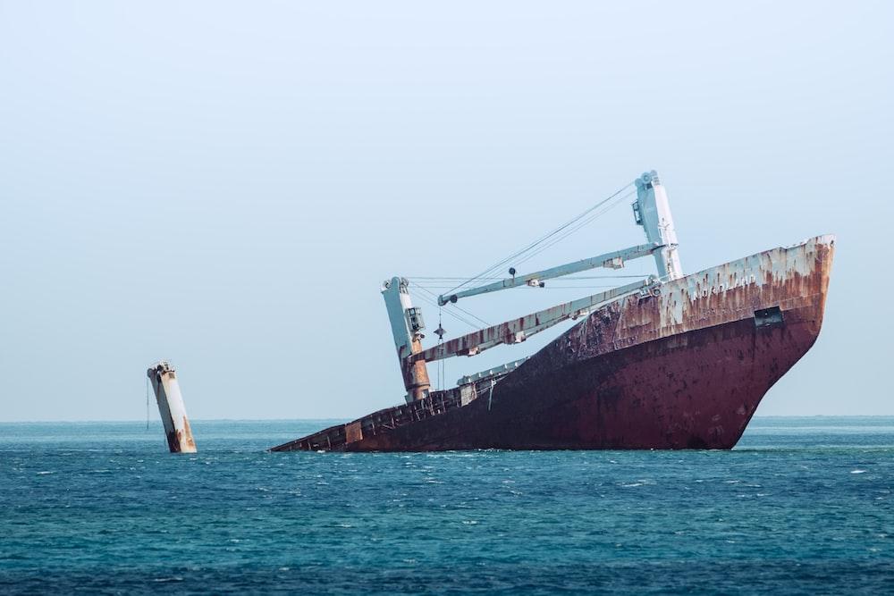 ship sinking on ocean at daytime