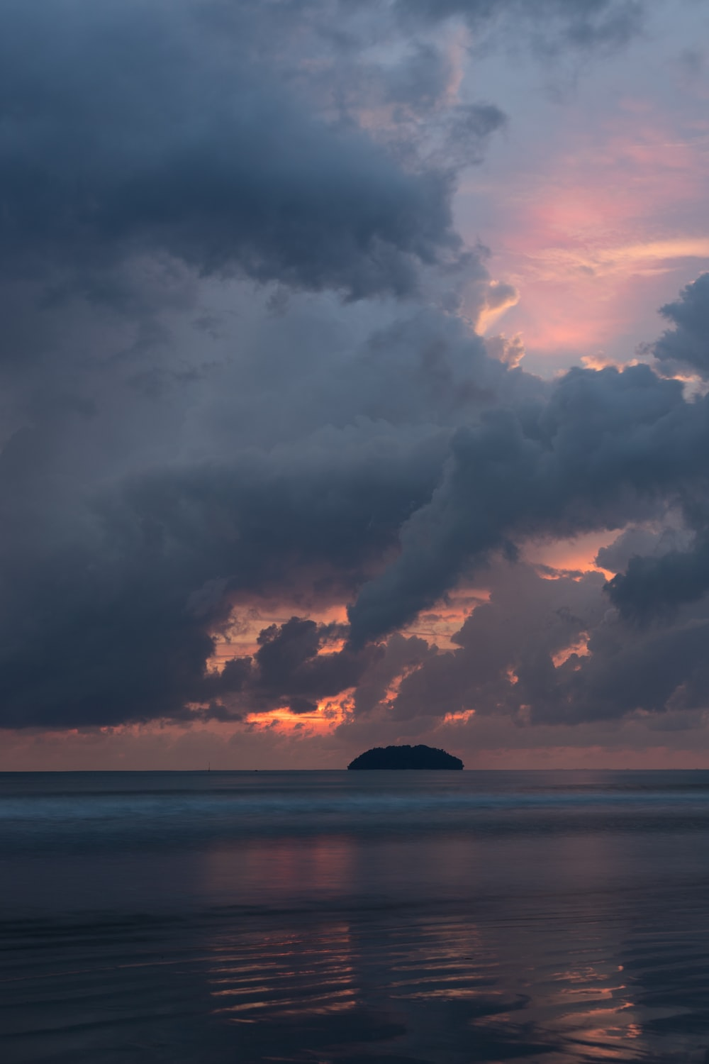 photo island under cloudy sky during golden hour