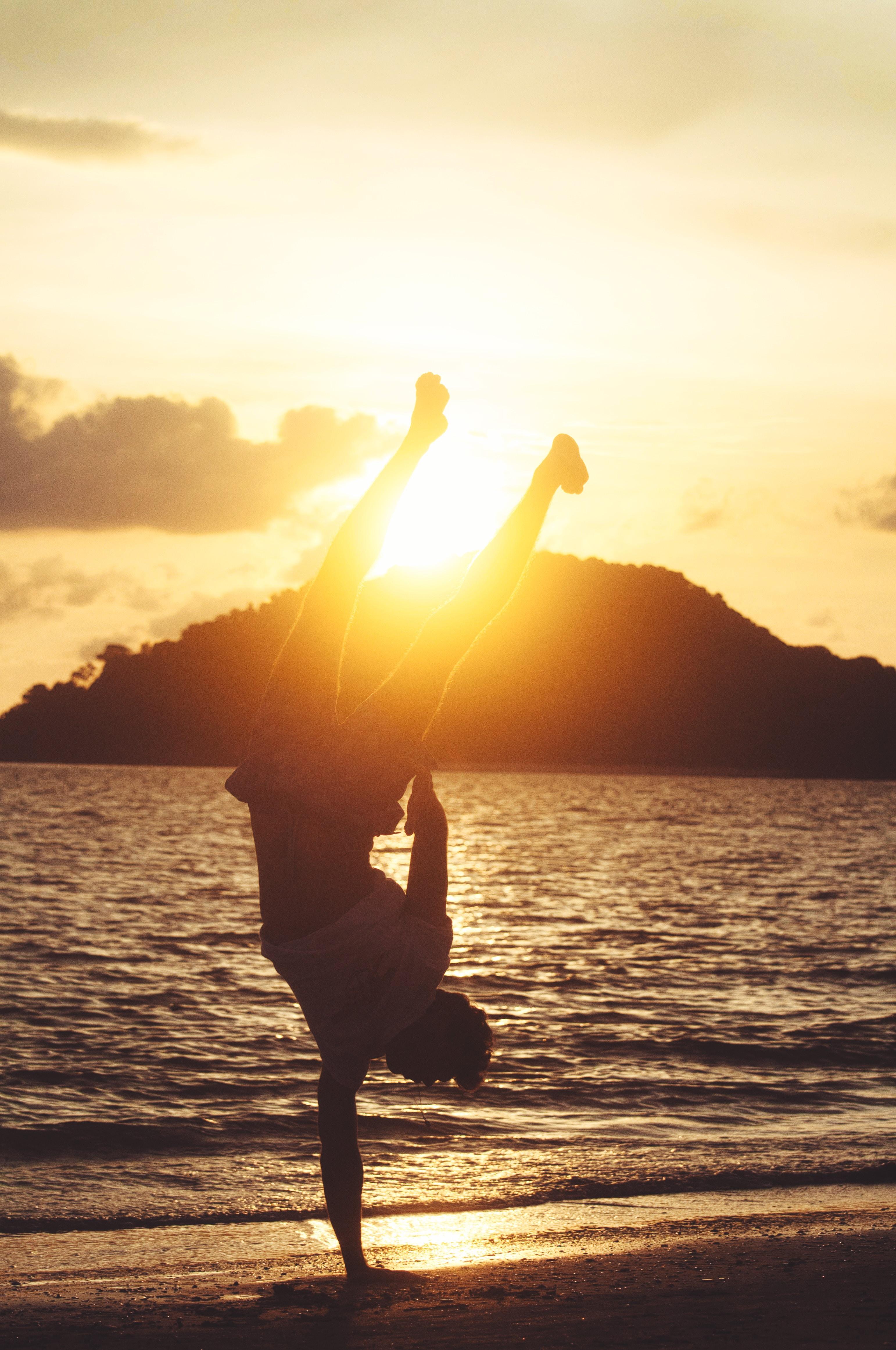 silhouette photo of man hand standing on seashore
