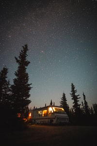 lighted white recreational vehicle into the woods