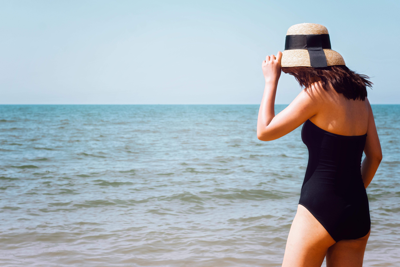 woman wearing black onepiece swimsuit standing beside seashore at daytime