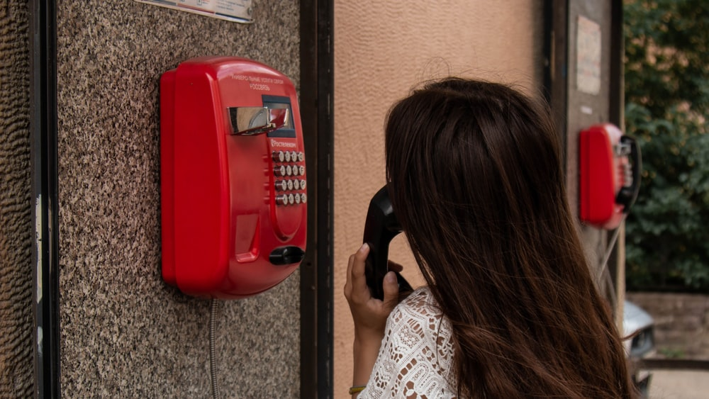 woman using payphone