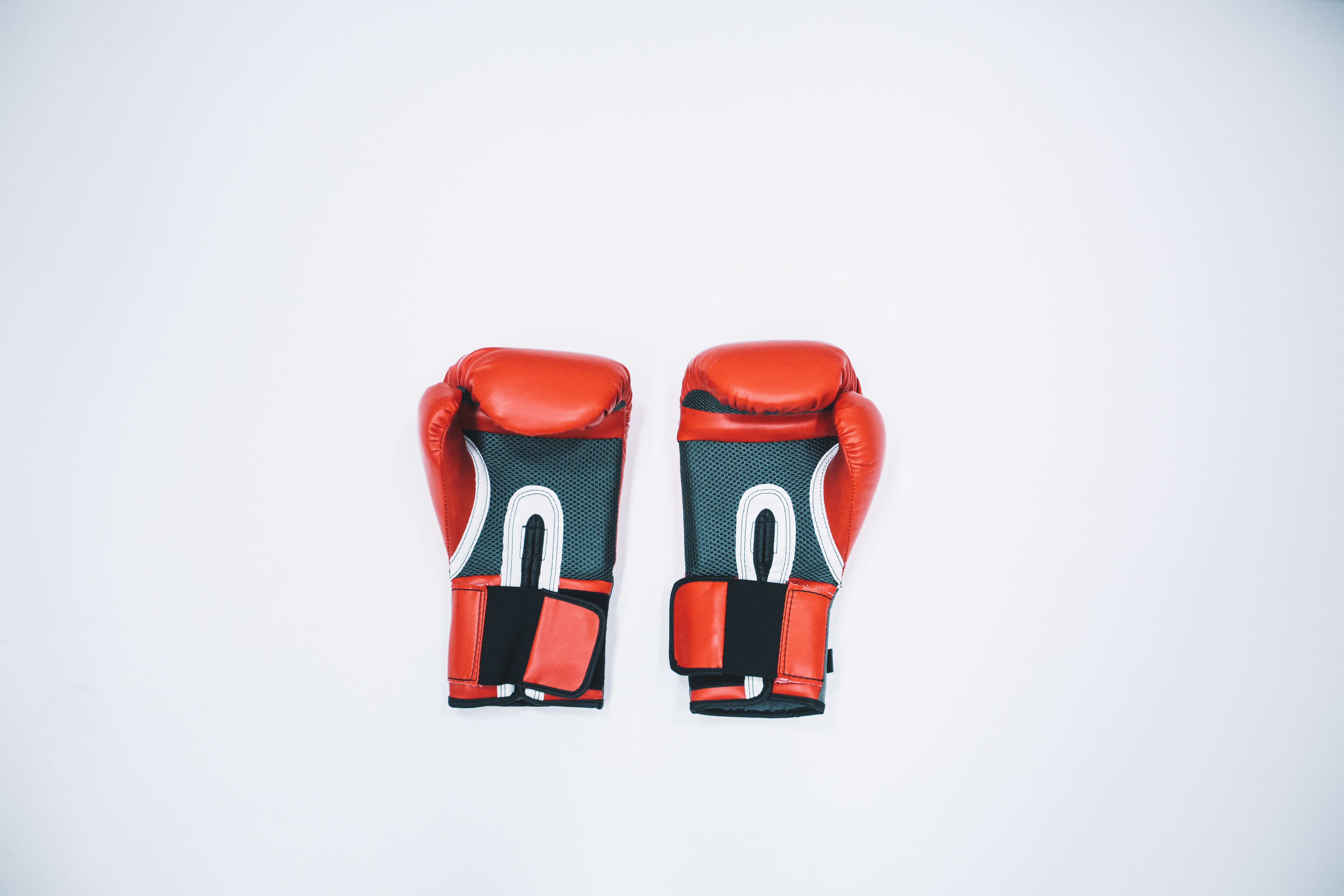 pair of red boxing gloves on white surface