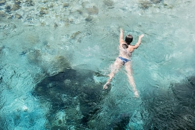 woman swimming in body of water albania zoom background