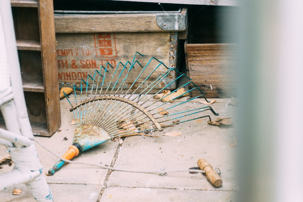 rake on pavement beside box