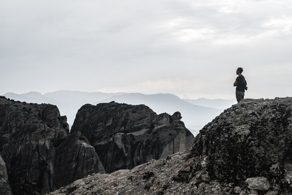 man standing on cliff wallpaper