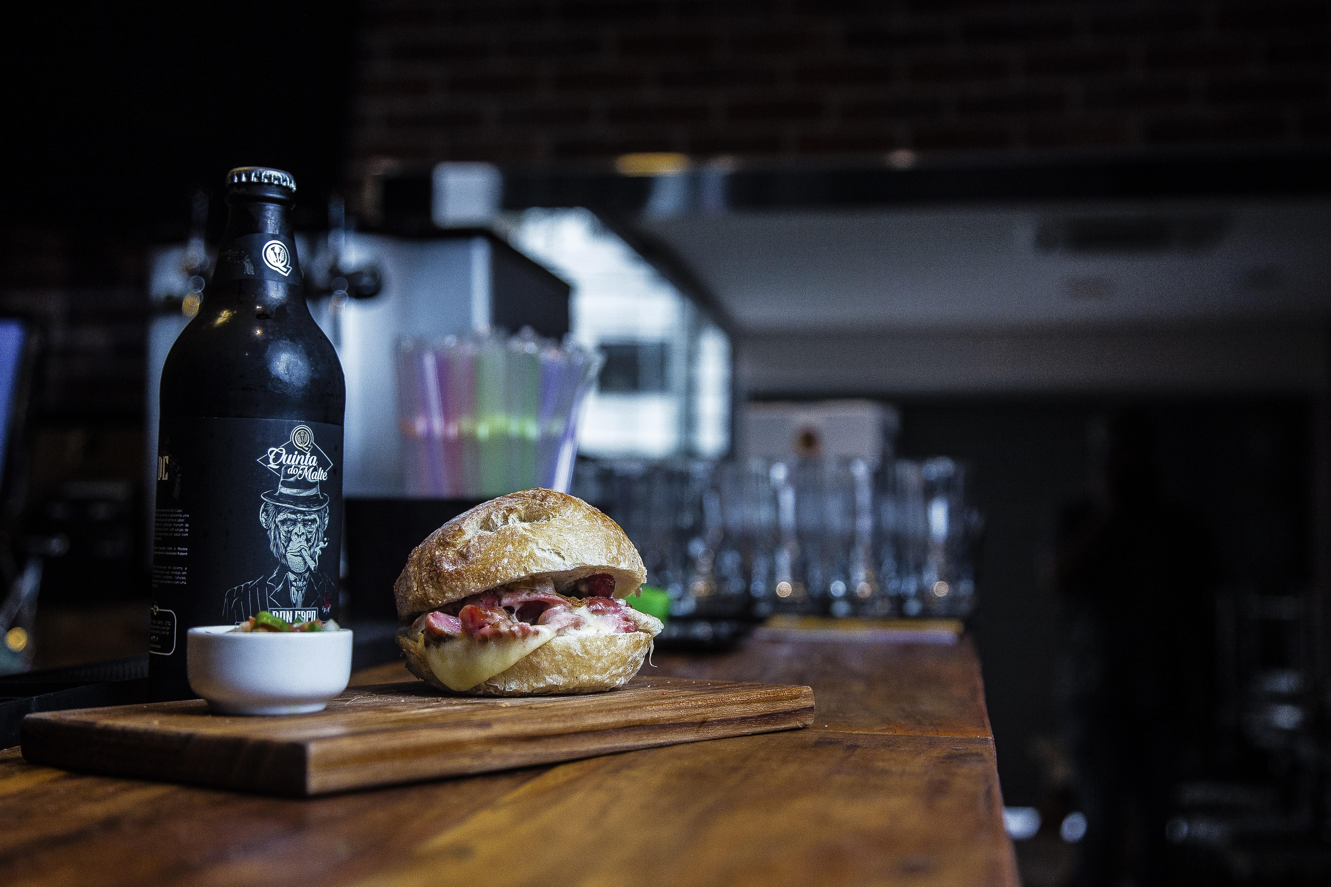 hamburger on chopping board near ceramic bowl and glass bottle