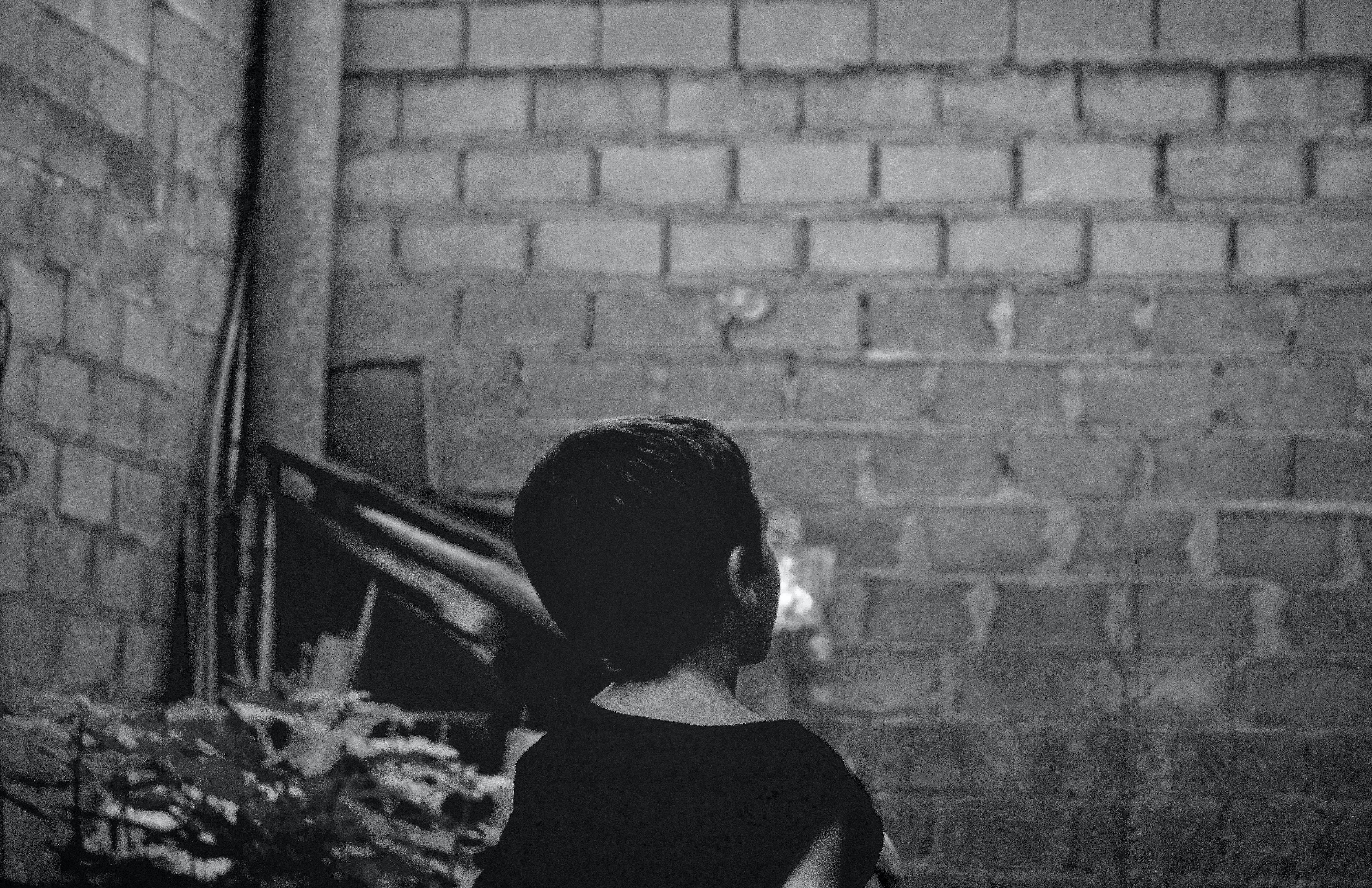 grayscale photo of boy standing near wall