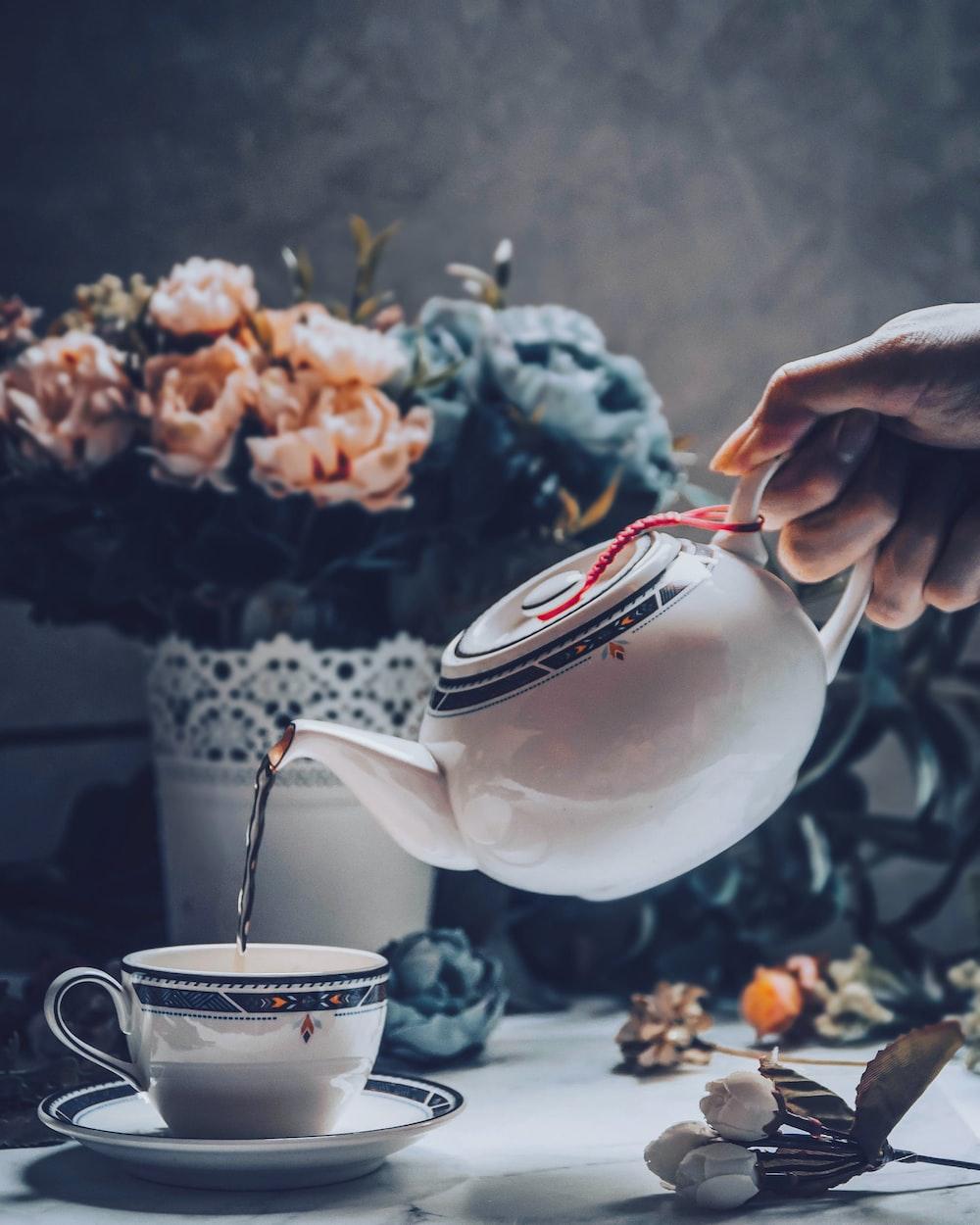 person holding white ceramic teapot