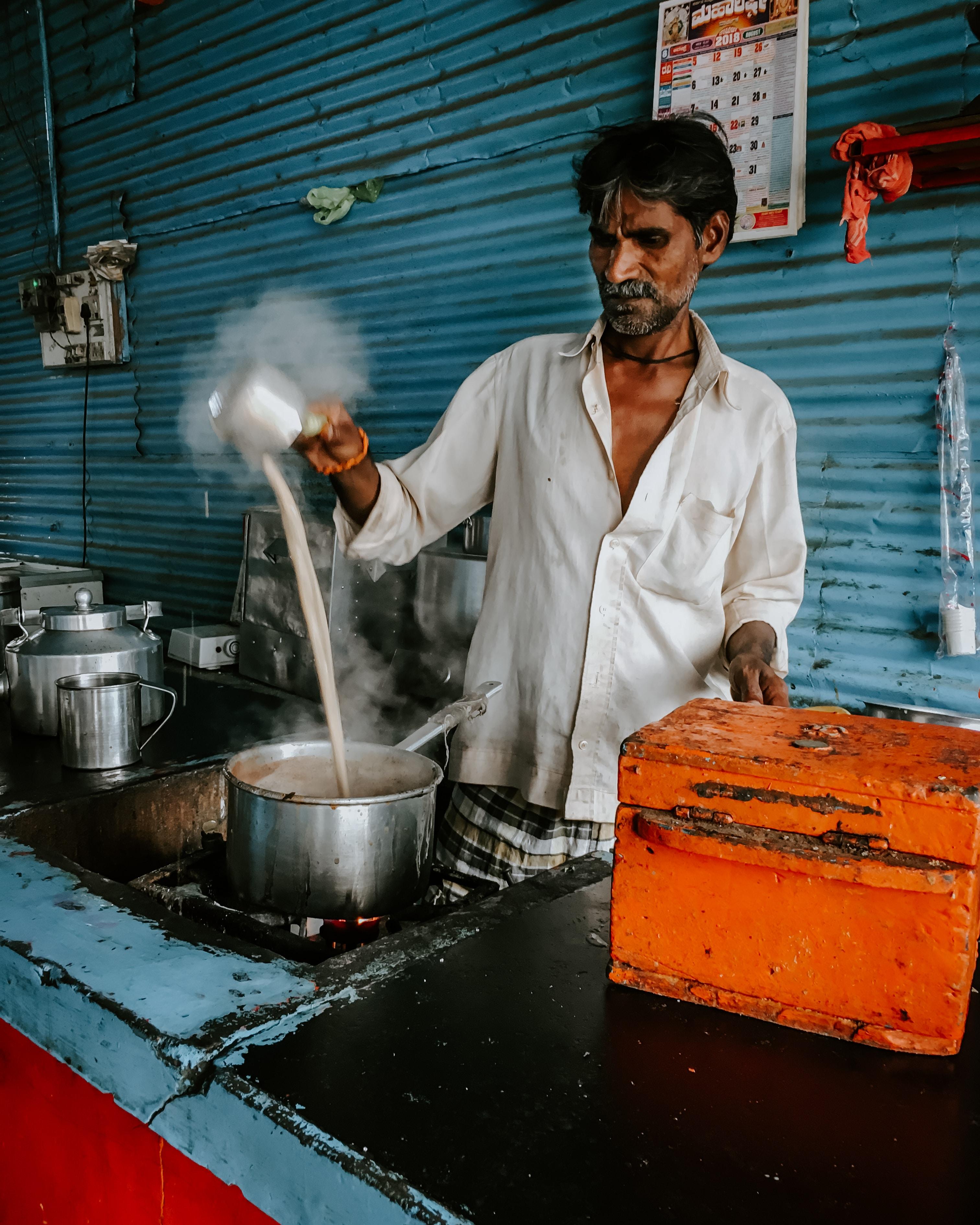 man pouring sauce on pot