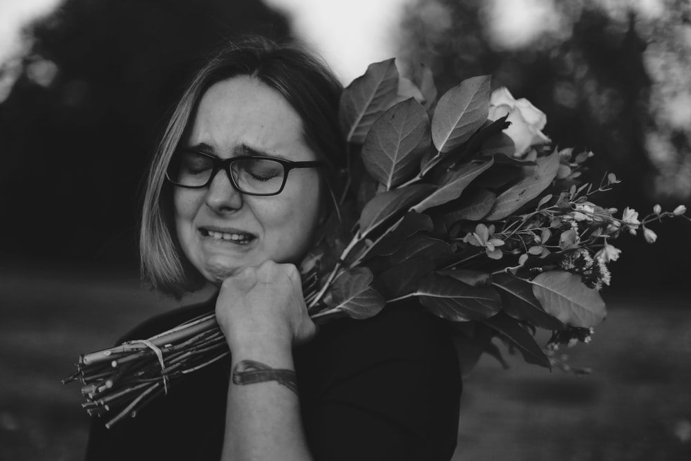 grayscale photo of crying woman holding bouquet of flowers