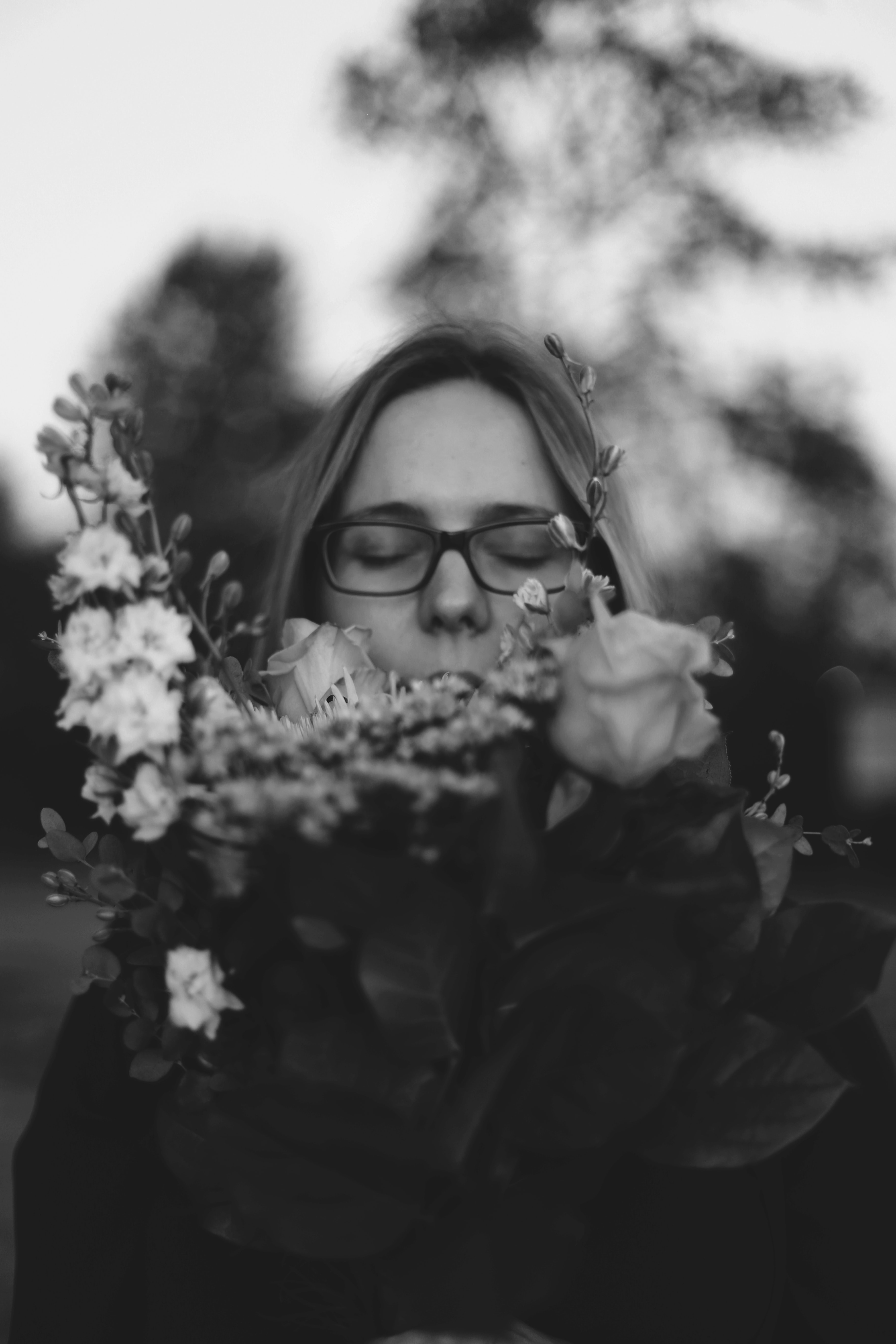 grayscale photo of woman smelling flower
