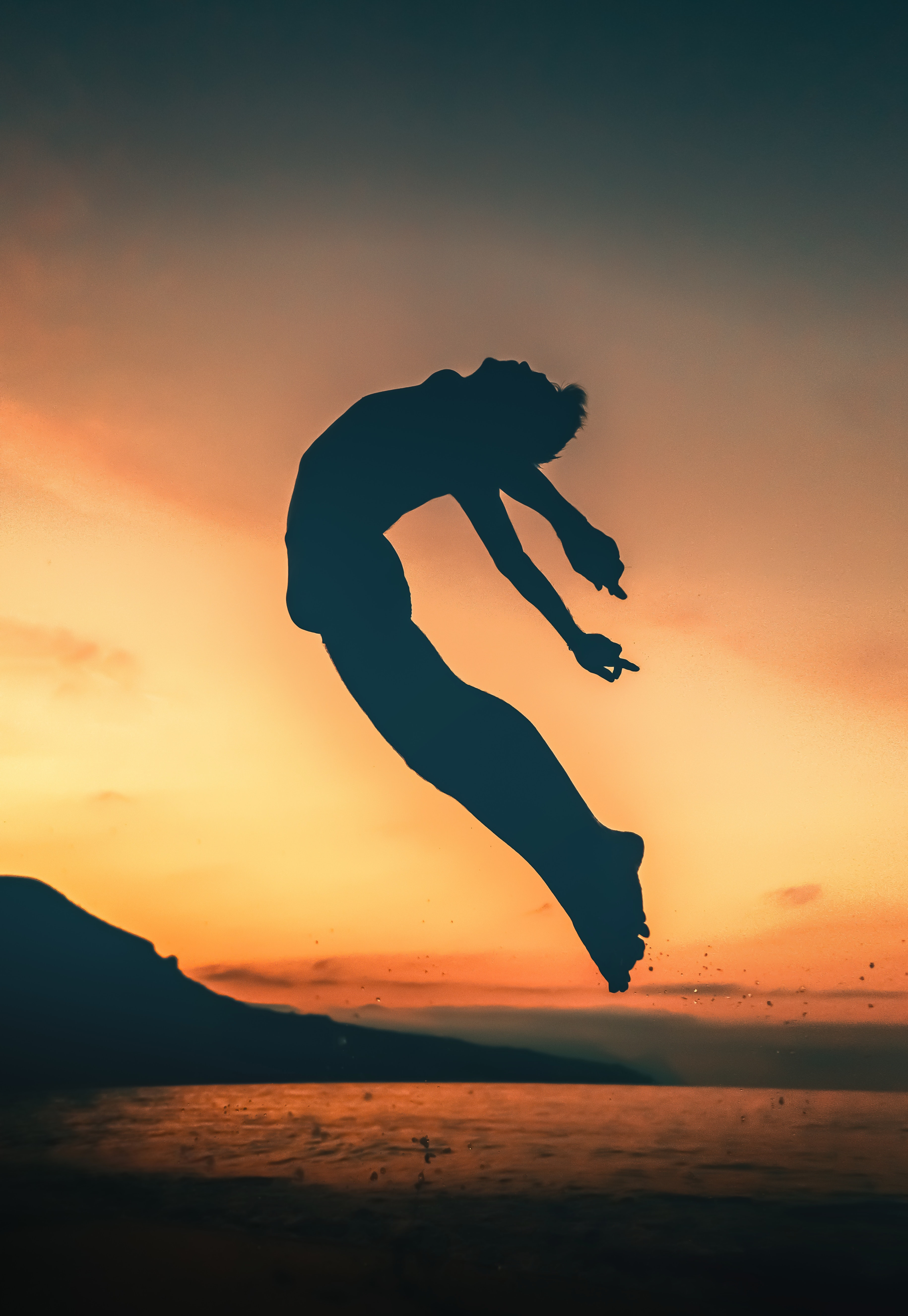 silhouette of person jumping on seashore