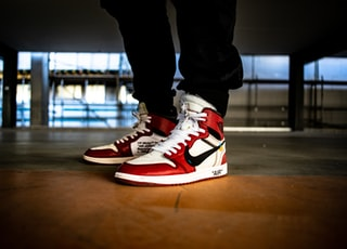 person wearing white-red-and-black Nike X Off-White Air Jordan 1's