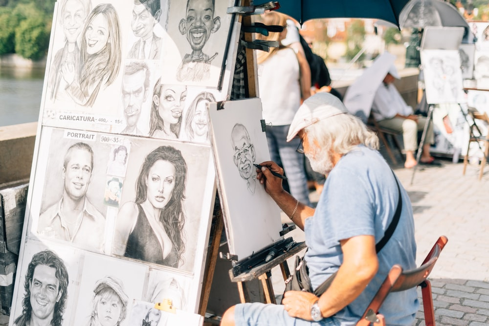 man sitting on chair sketching a person's face