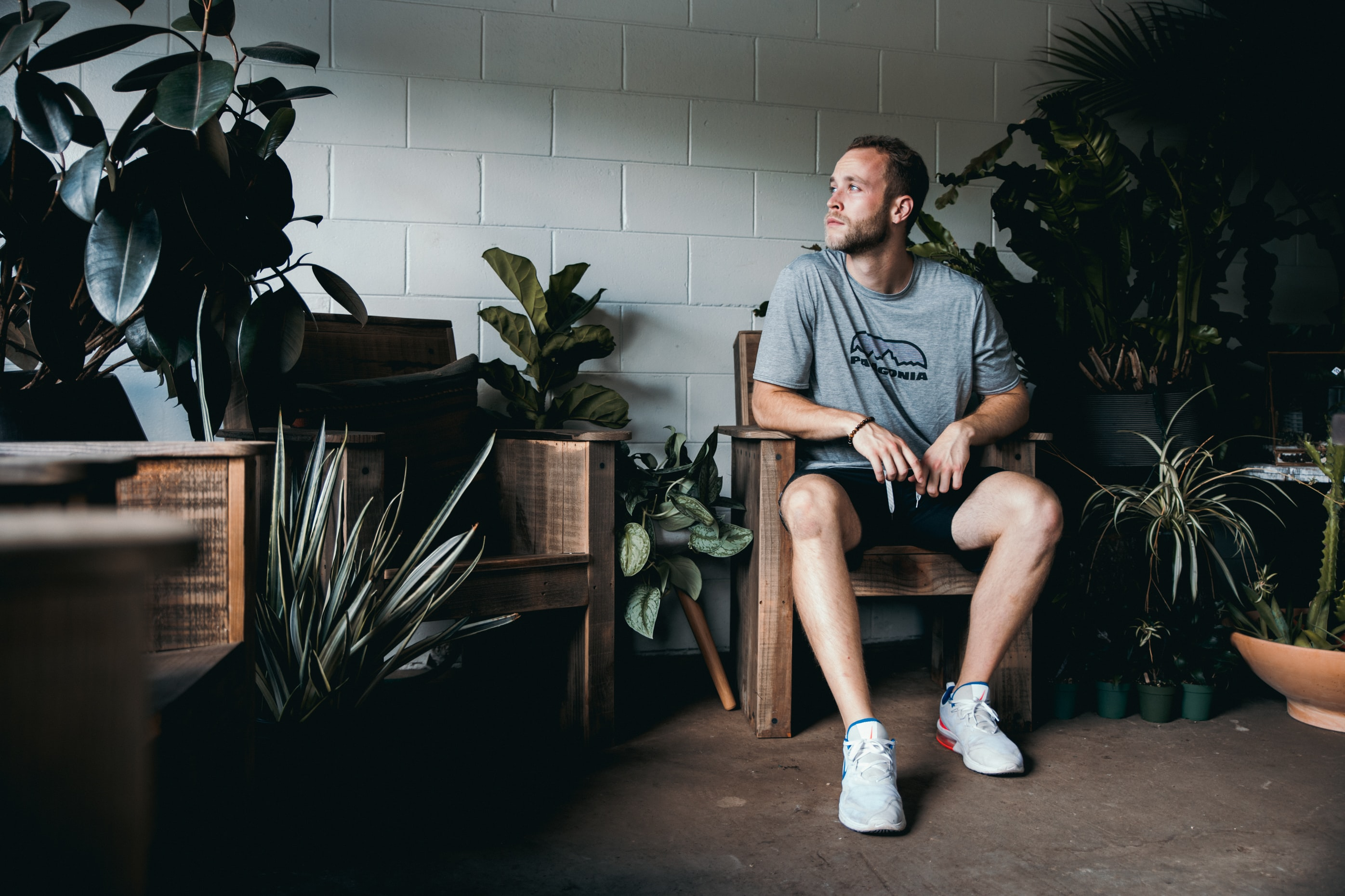 seated man between potted plants in front of while wall