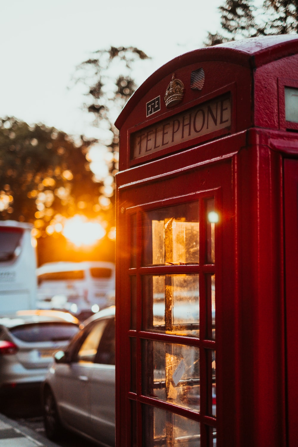 selective focus photography of red telephone booth near car