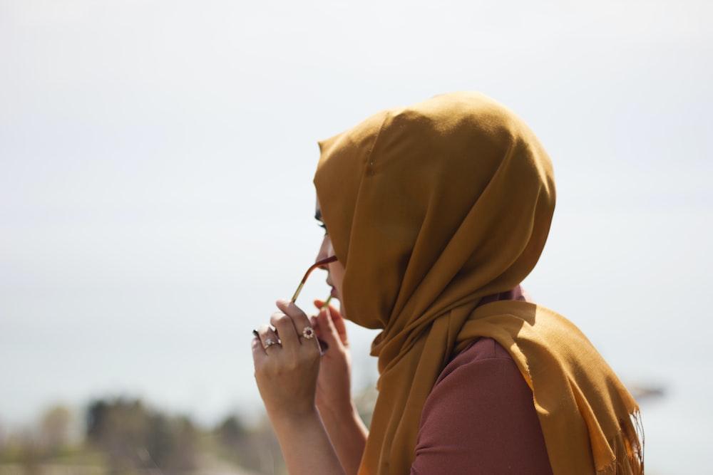 woman in brown headdress putting eyeglasses in tilt shift photography