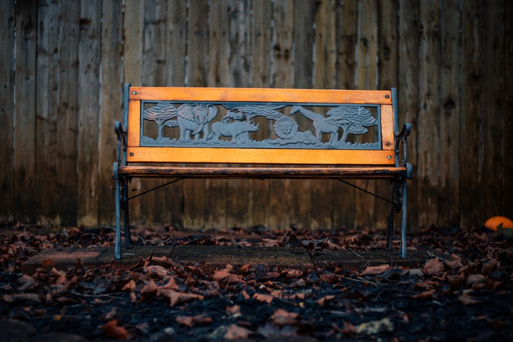 brown and black metal framed bench beside brown wooden fence