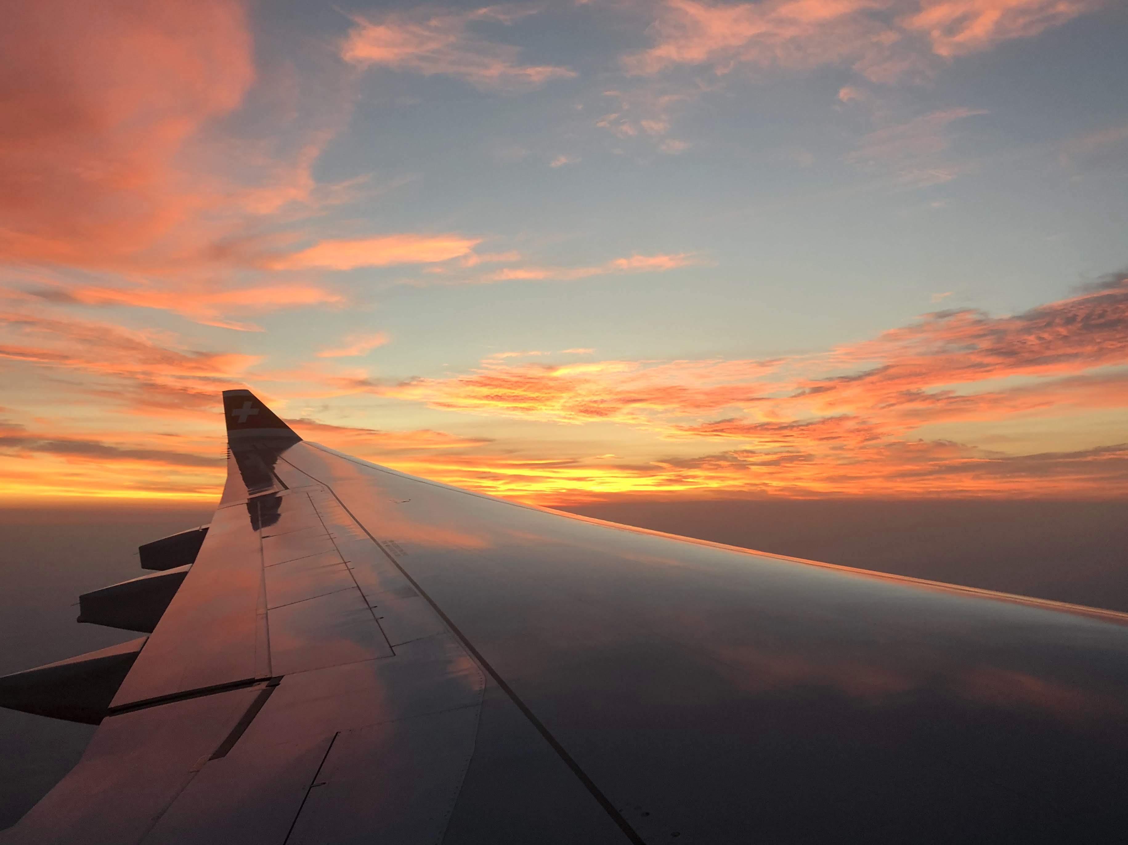 gray aircraft flying during orange sunset
