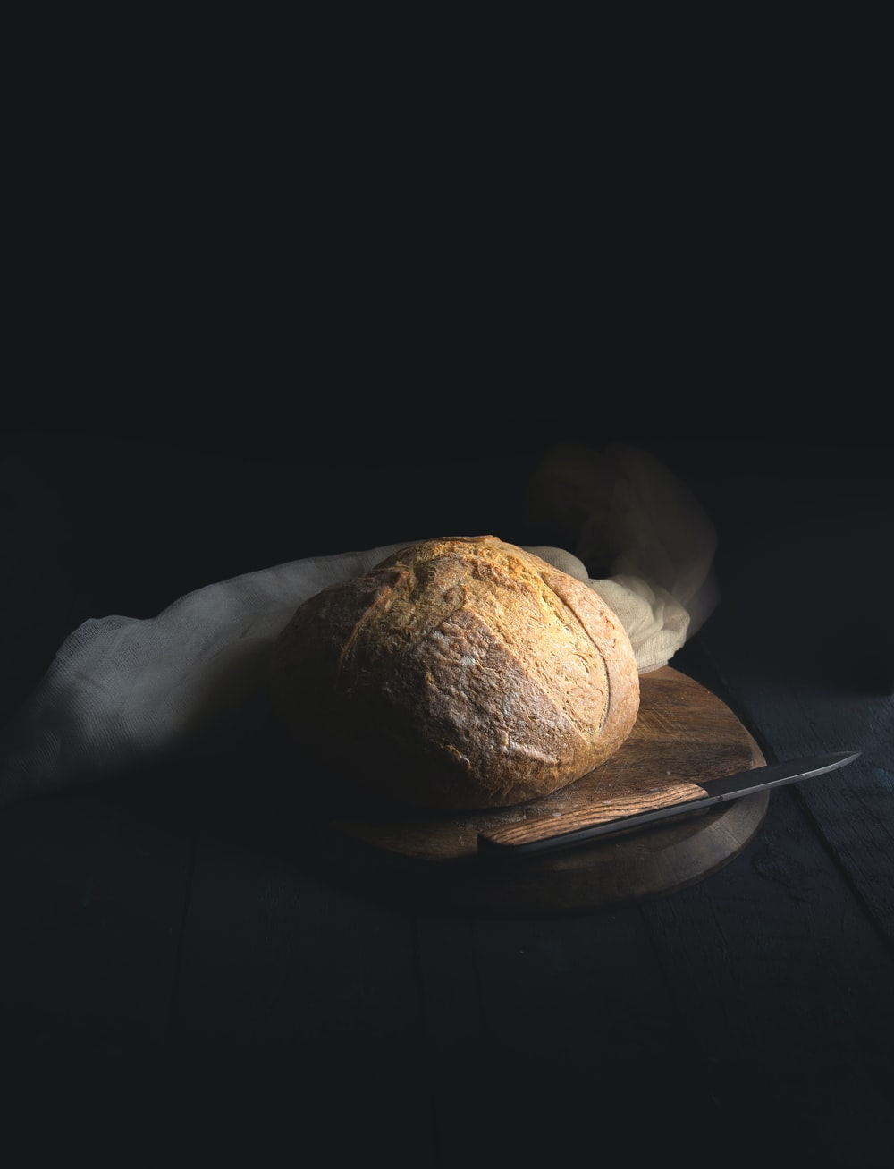 baked bread beside knife on wooden board