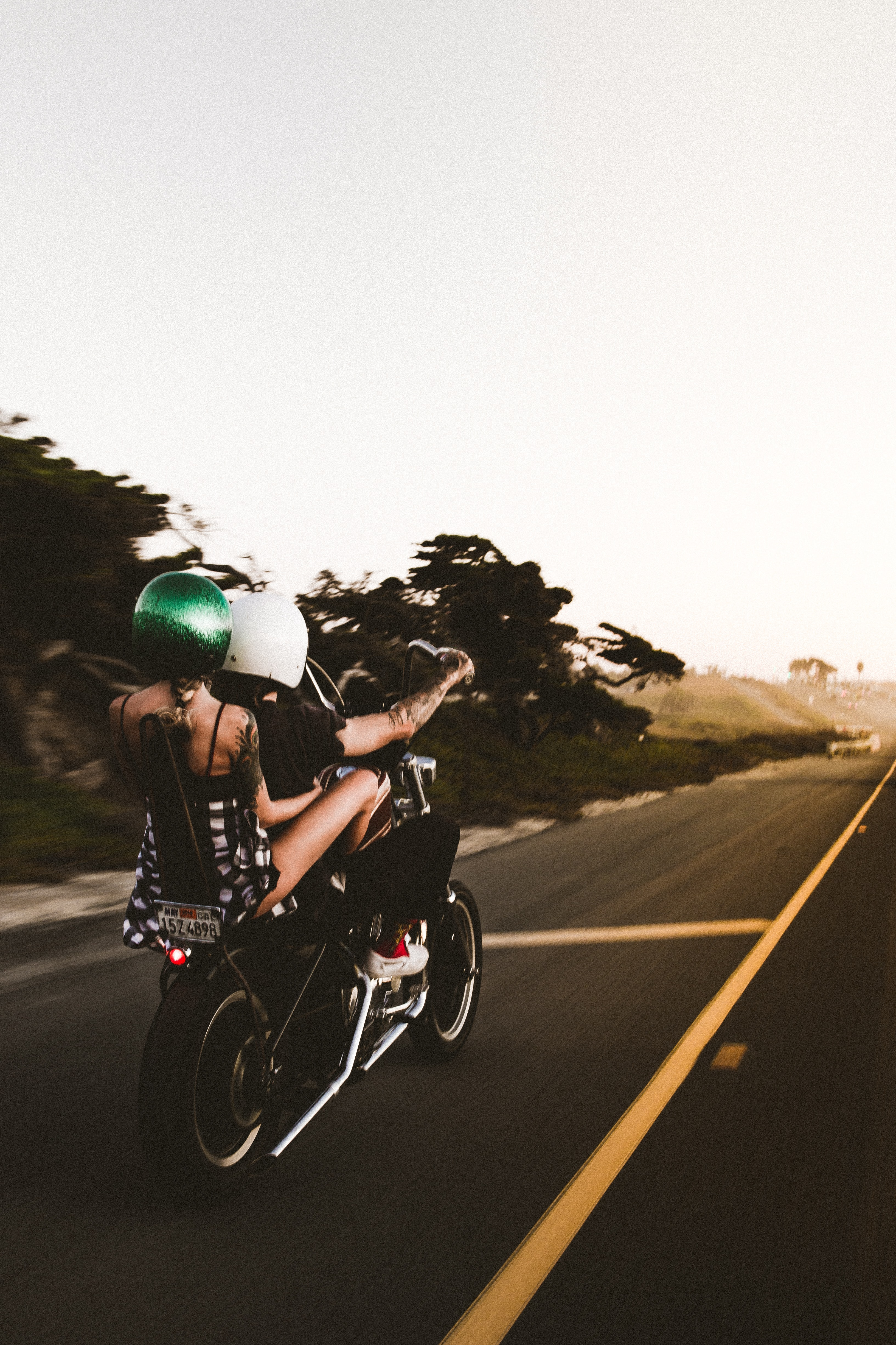 man driving on motorcycle with woman