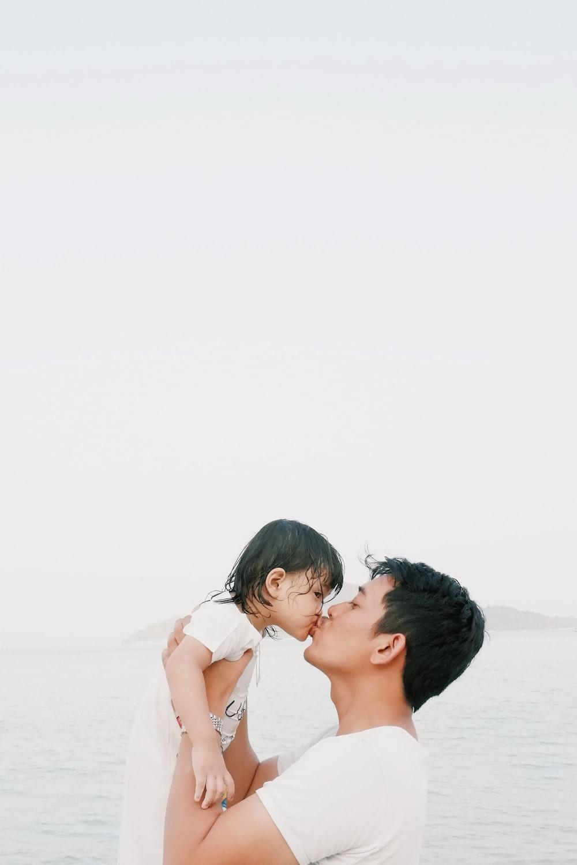 man kissing toddler during daytime