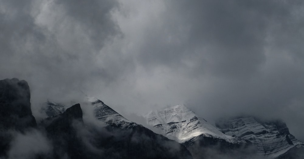 grayscale photography of mountain covered with fog