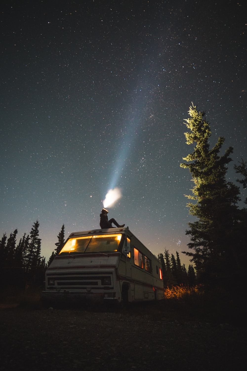 person sits on top of van at night