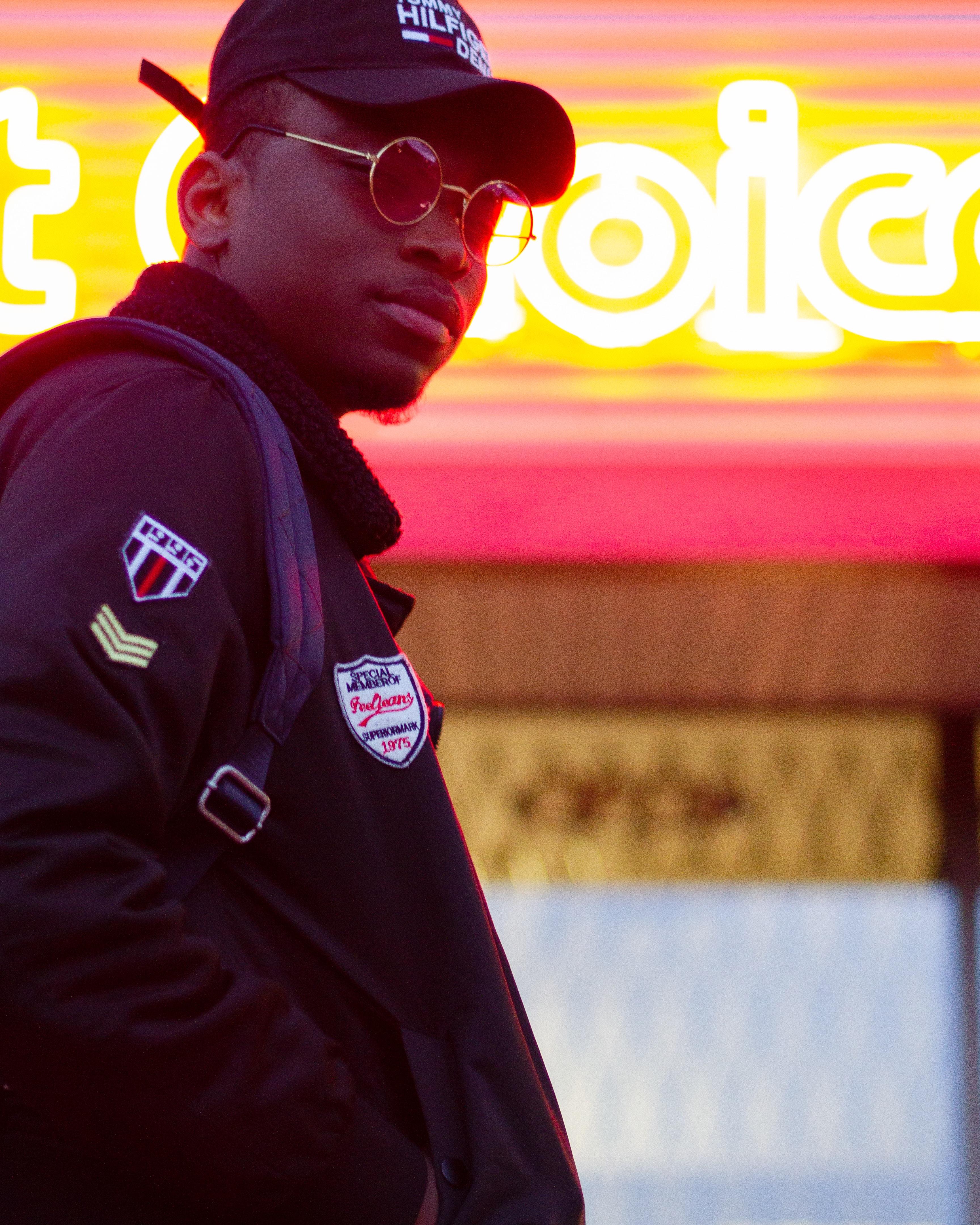 man wearing black jacket near lighted signboard