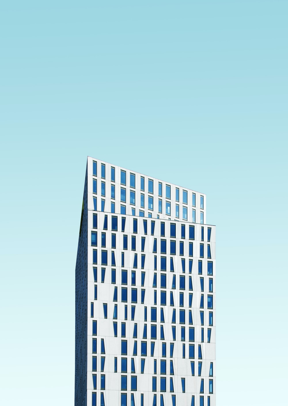 photo of white concrete building under blue sky at daytime