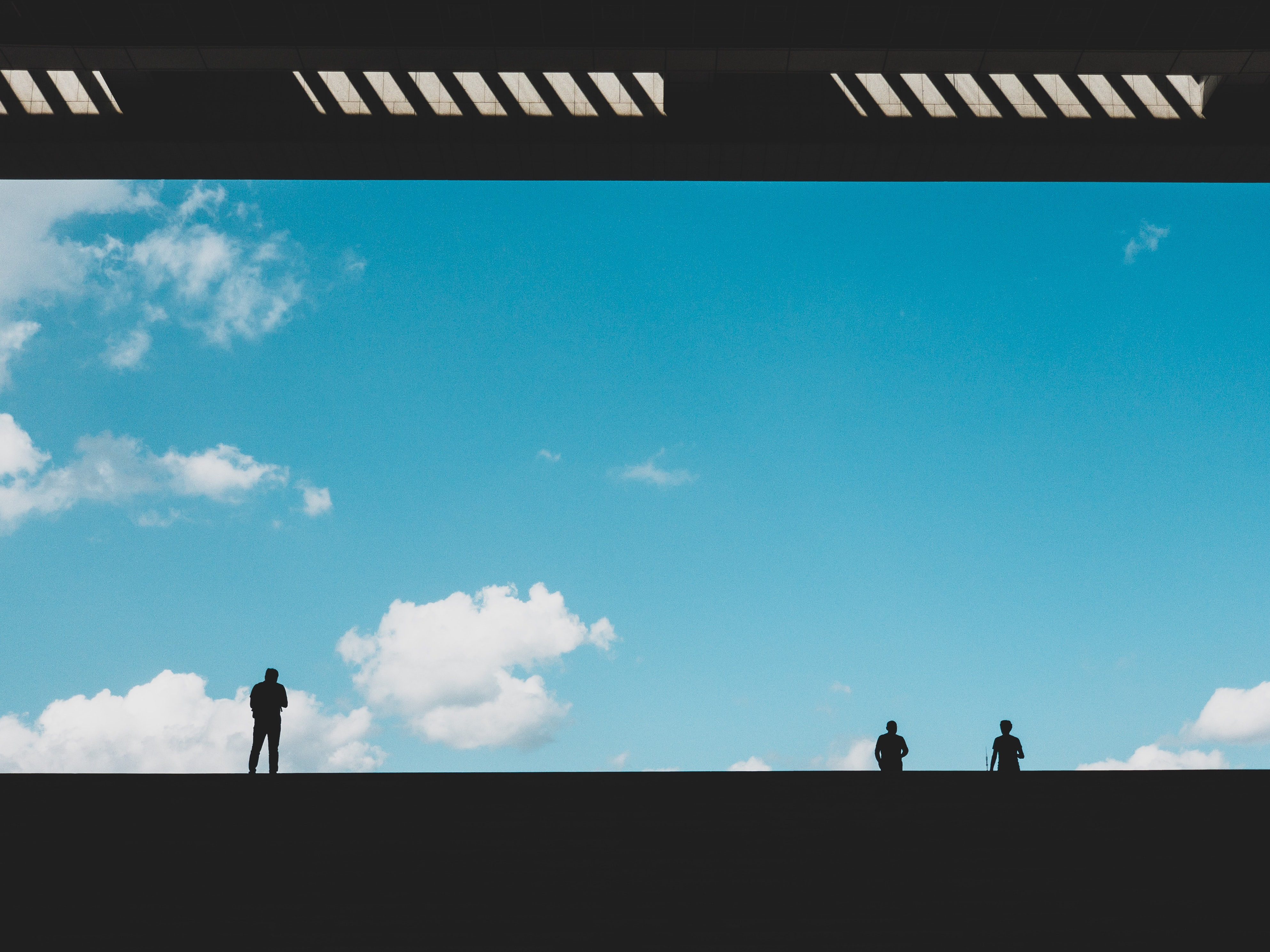 silhouette of three person against blue sky