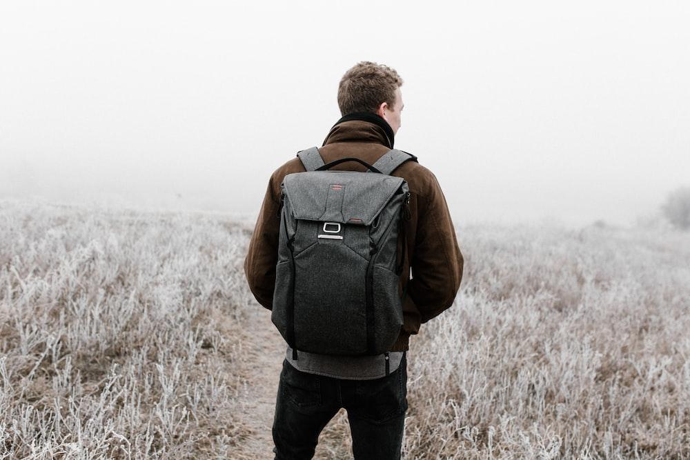 man wearing backpack walking on pathway