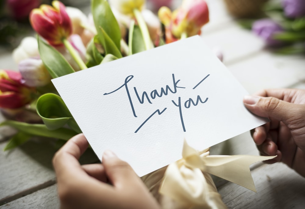 person holding white card with thank you handwritten text