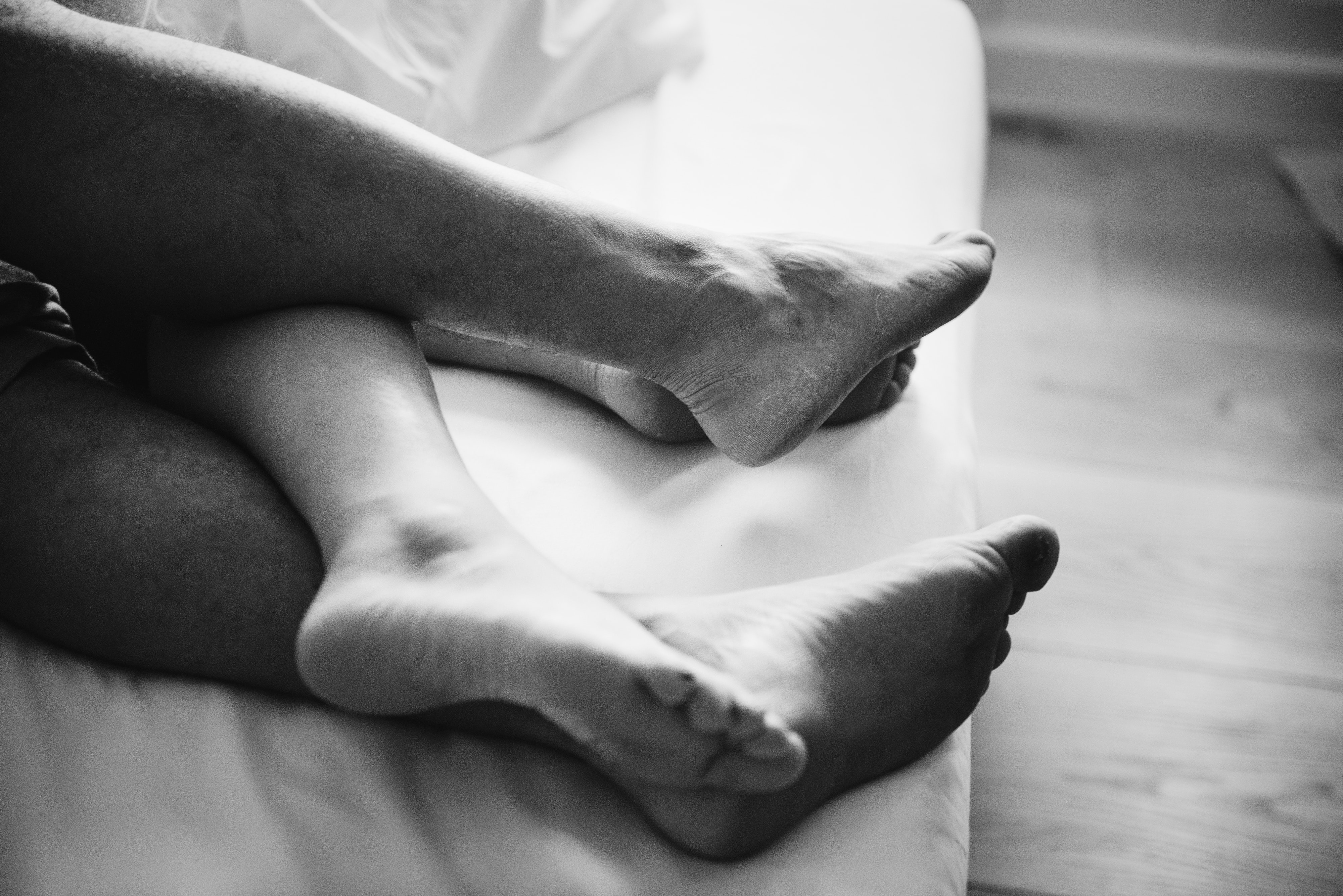grayscale photography of person's feet on bed