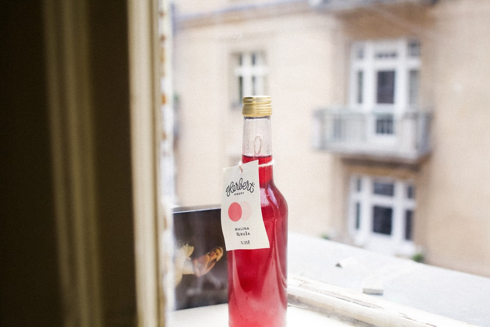 selective focus photography of bottle filled with red liquid on windowsill