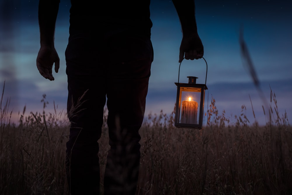 silhouette photo of man carrying candle lantern with lighted candle