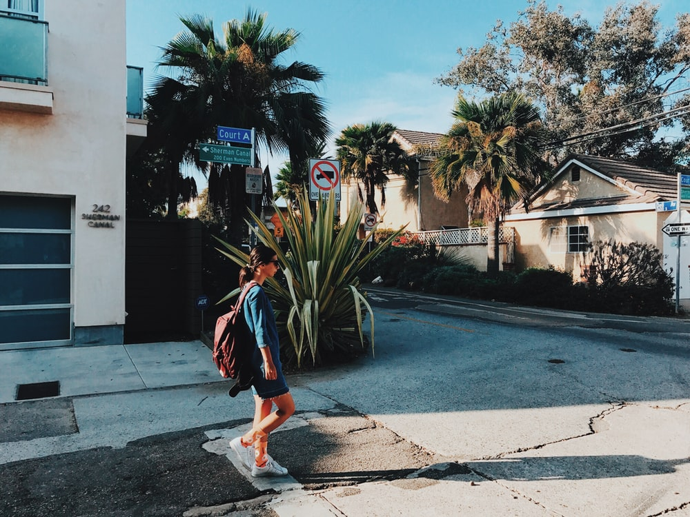 walking woman with backpack near house at daytime