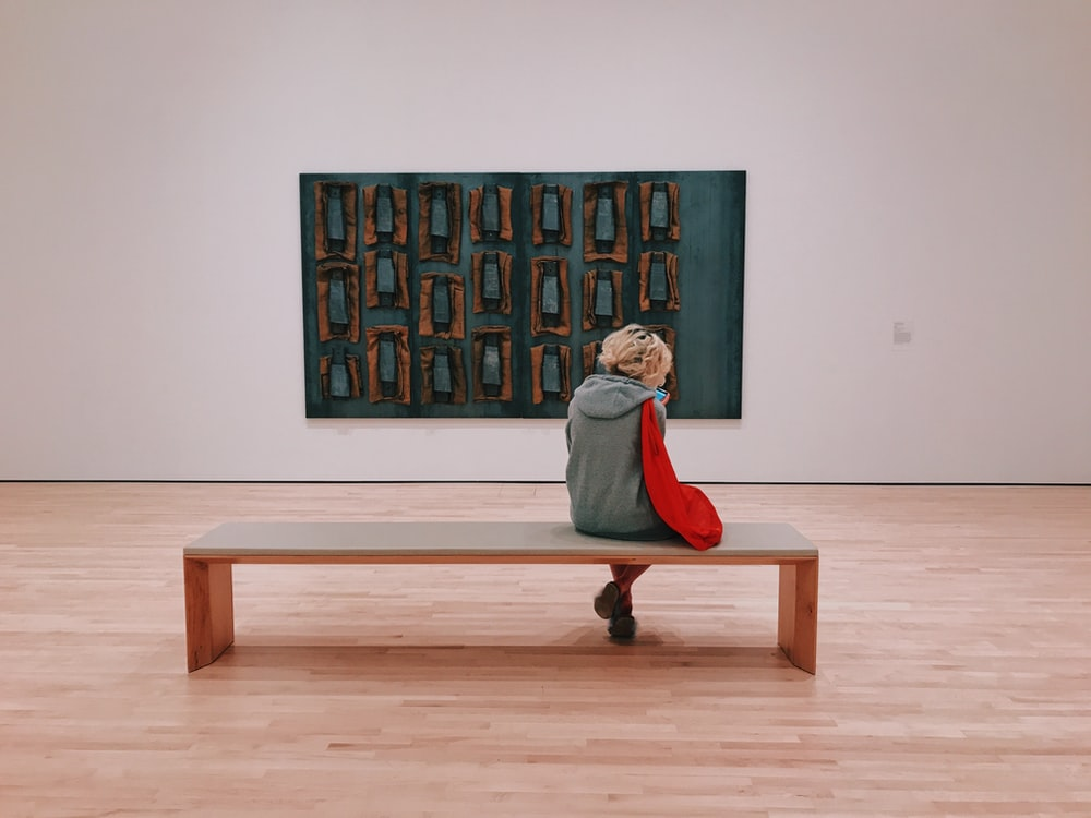 person sitting on bench ion front of painting