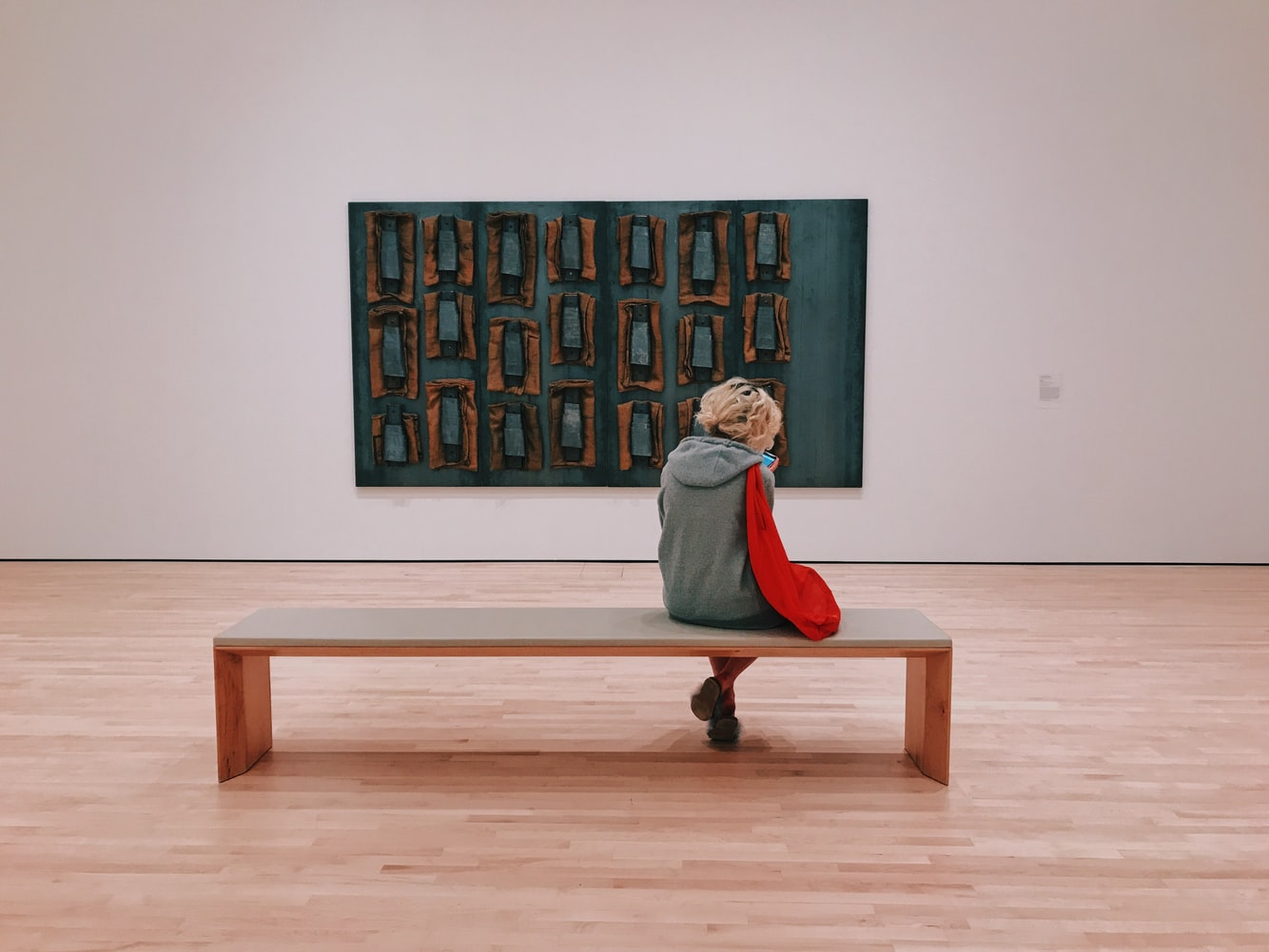 Back view of a person sitting on a bench in a museum, looking at a painting.