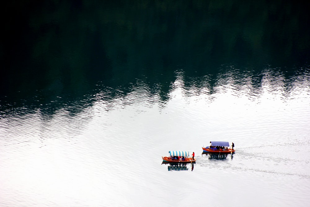 people on two boats on lake