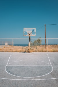 gray basketball field near body of water
