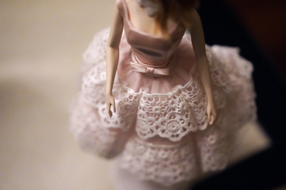 close-up of female doll wearing pink and white dress