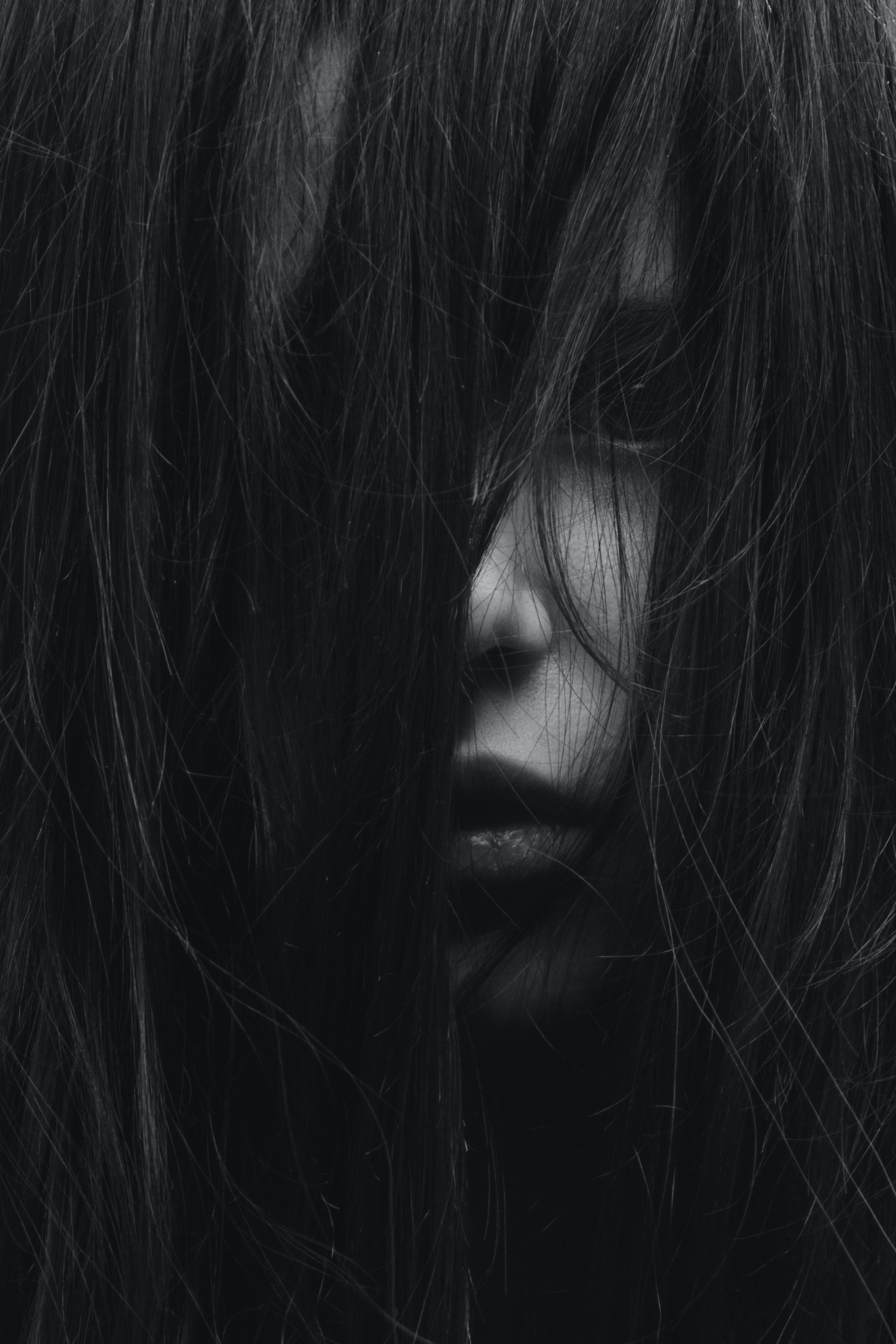 grayscale photography of girl covered her face with hair