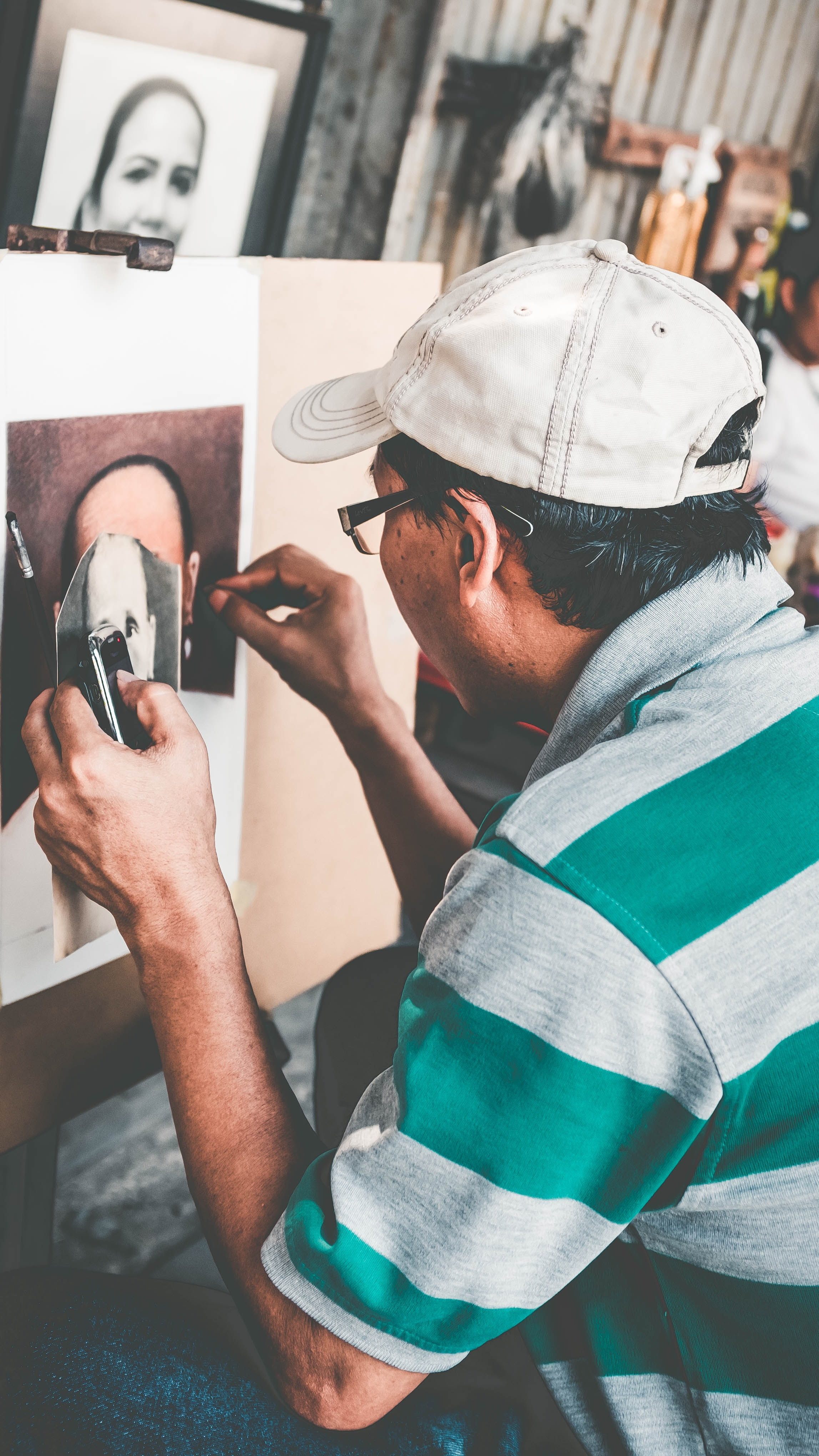 person holding photo while painting