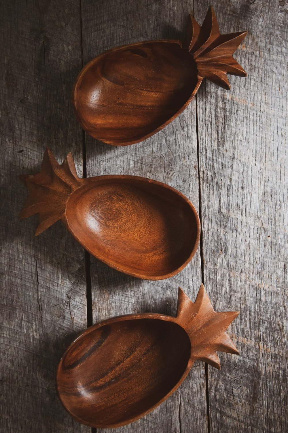 three brown wooden bowls on gray wood
