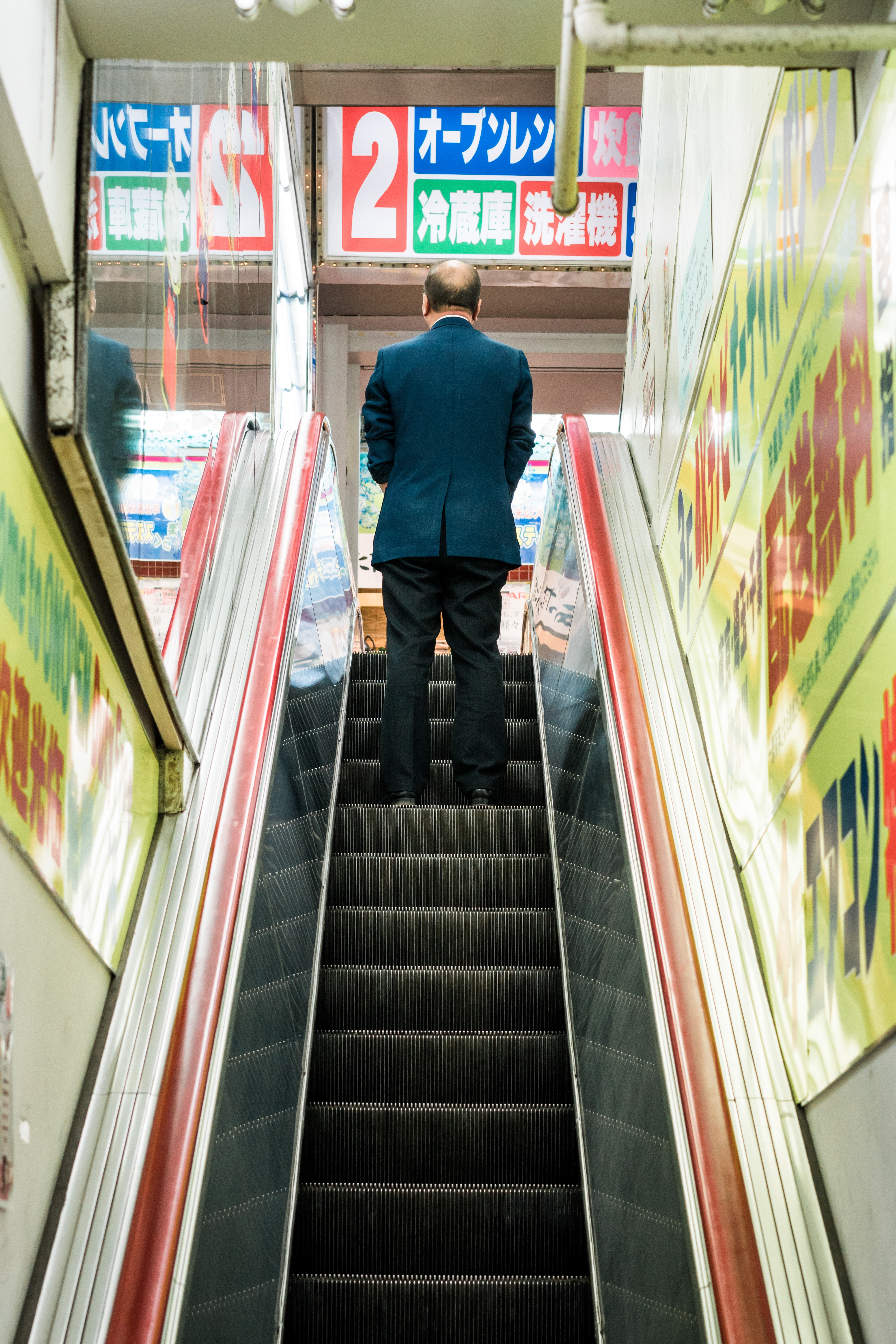 man in blue suit jacket standing on escalator