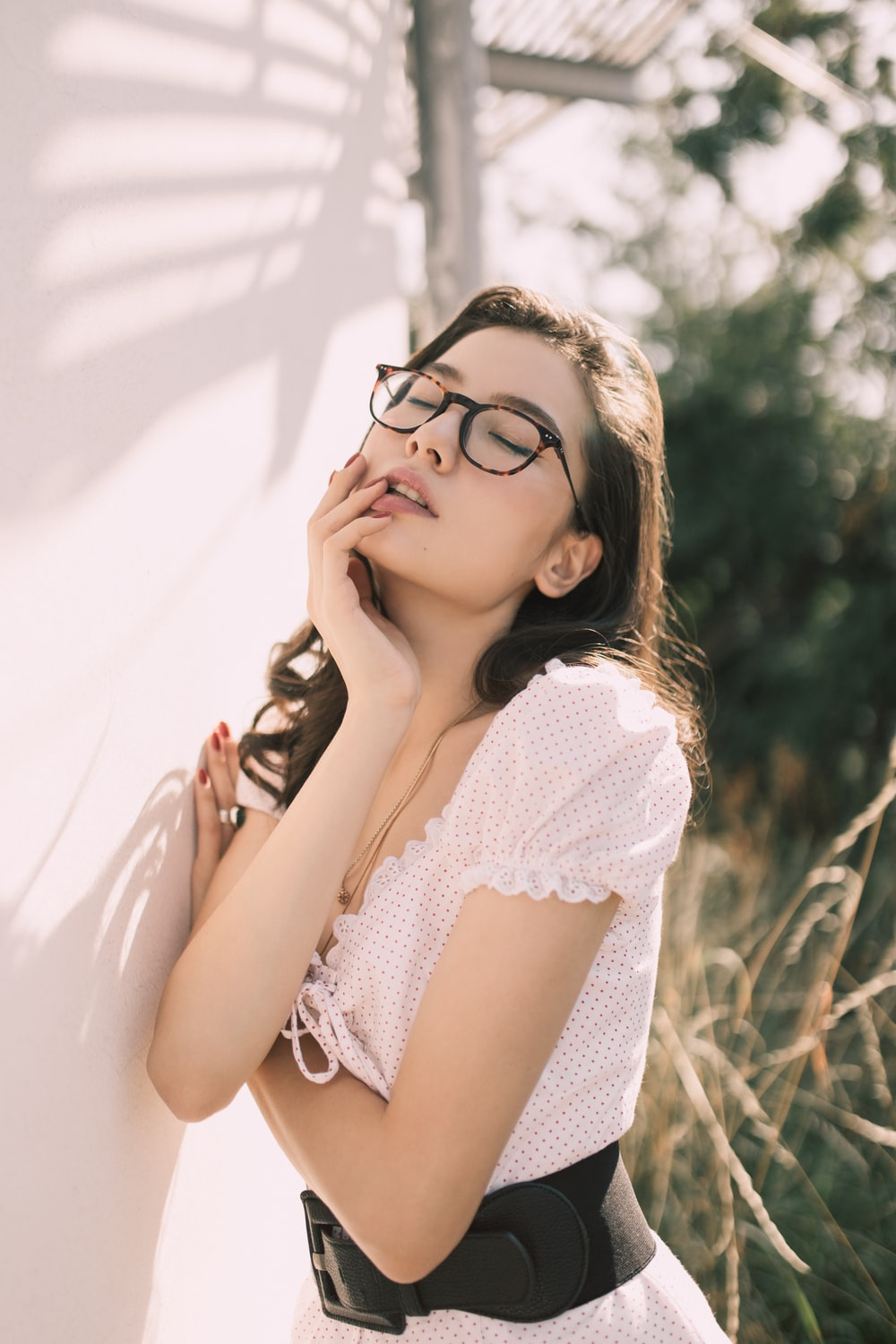 woman in white and black top wearing eyeglasses