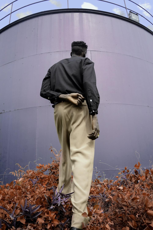 man standing facing tank
