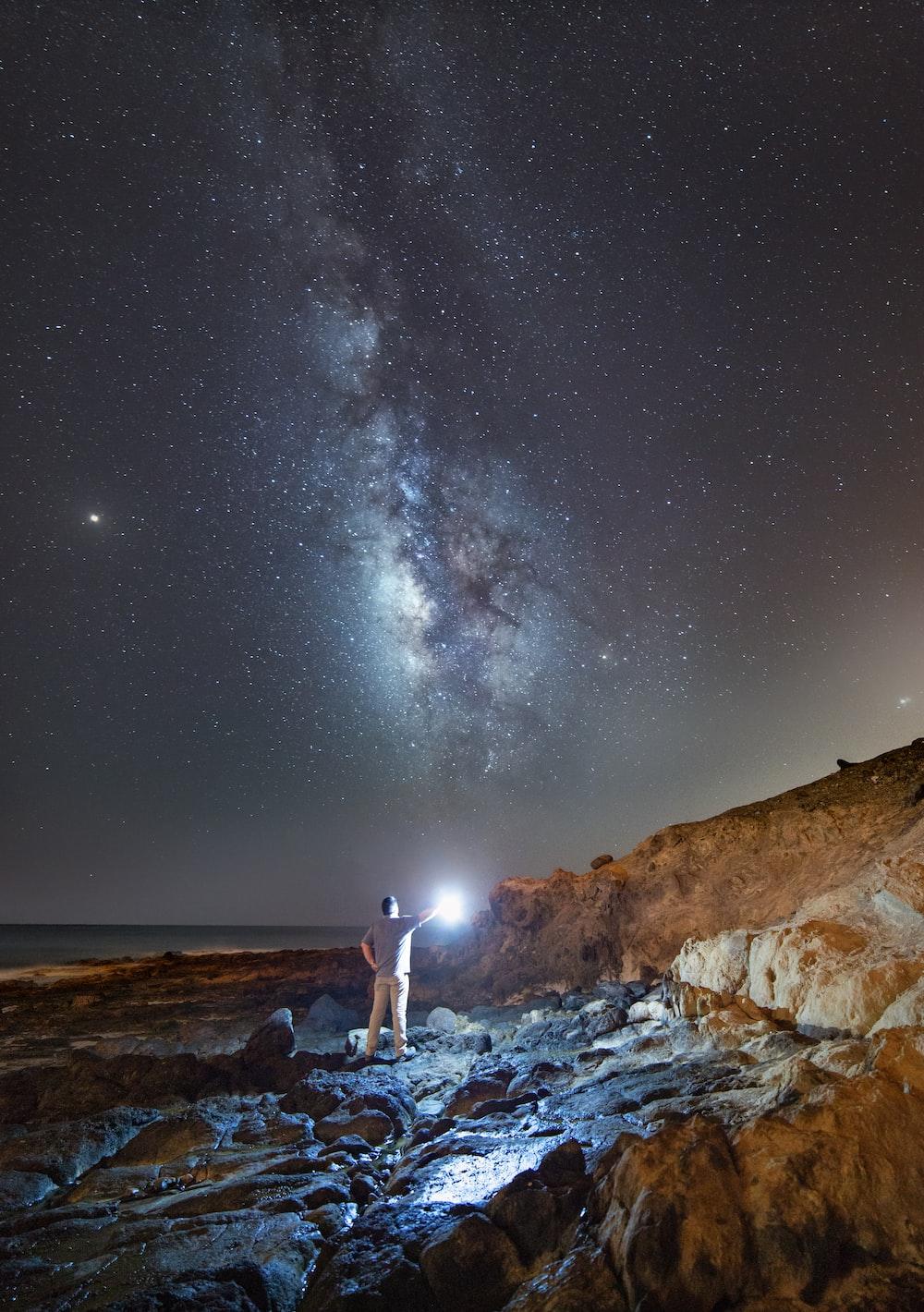 man holding light under night sky